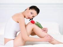 Vrouw met rode tulp op benen Royalty-vrije Stock Afbeelding