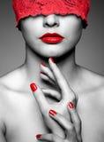 Vrouw met rood kanten lint op ogen Stock Foto's