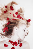 Vrouw met roze bloemblaadjes in haar haar Stock Foto