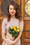 Vrouw met rozen die zich dichtbij oude deur bevinden Stock Afbeelding