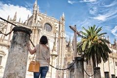 Vrouw met rug tegen een kolom die de Kathedraal van Sevilla bekijken stock fotografie