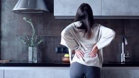 Vrouw met rugpijn in keuken stock videobeelden