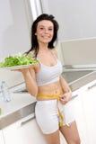 Vrouw met salade in keuken Stock Foto's