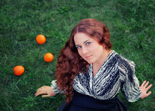 Vrouw met sinaasappelen Stock Foto