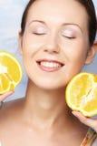 Vrouw met sinaasappelen in haar handen Stock Fotografie