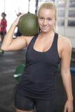 Vrouw met slagbal op het centrum van de geschiktheidsgymnastiek Royalty-vrije Stock Foto's