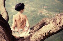 Vrouw met slang terug tatoegering op haar Stock Afbeelding