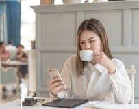 vrouw met slimme telefoon en koffie stock foto's