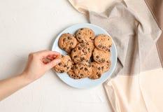 Vrouw met smakelijke chocoladeschilferkoekjes op grijze achtergrond, hoogste mening stock foto's