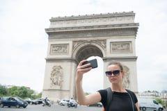 Vrouw met smartphone bij boogmonument in Parijs, Frankrijk De vrouw maakt selfie met telefoon in arc DE triomphe Vakantie en sigh stock foto's
