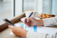 Vrouw met smartphone en grafiek bij koffie Stock Afbeeldingen