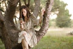 Vrouw met Smartphone op een Boom stock foto's
