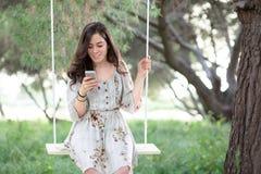 Vrouw met Smartphone op een Schommeling royalty-vrije stock afbeelding