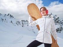 Vrouw met snowboard tegen wit sneeuwlandschap stock afbeelding