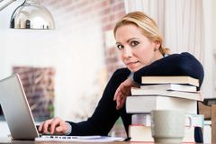 Vrouw met stapel boeken die laptop met behulp van stock fotografie