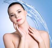 Vrouw met stroom dalend water op blauw Royalty-vrije Stock Foto's