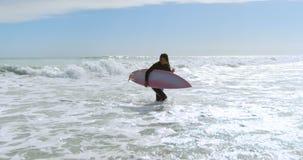 Vrouw met surfplank die op het overzees 4k lopen stock footage