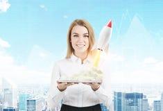 Vrouw met tablet en kleine raket, stad Stock Afbeeldingen