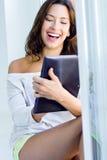 Vrouw met tablet thuis stock afbeeldingen