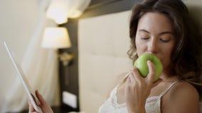 Vrouw met tabletpc en een appel in bed stock video