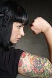 Vrouw met tatoegering en vuist Stock Foto's