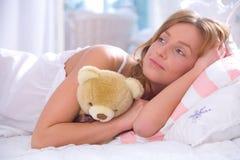 Vrouw met teddybeer in bed Stock Foto's