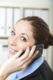 Vrouw met telefoon bij haar bureau Stock Fotografie