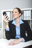 Vrouw met telefoon bij haar bureau Stock Foto's