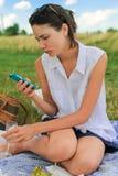 Vrouw met telefoon die rust hebben stock afbeelding