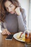 Vrouw met telefoon en sandwich Royalty-vrije Stock Foto