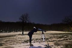 Vrouw met telescoop onder de hemel van de de winternacht kent zij de manier Stock Foto
