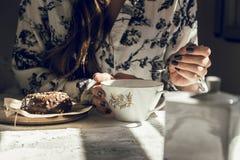 Vrouw met theekop, en chocoladedoughnut, die bij de lijst zitten B Stock Afbeeldingen