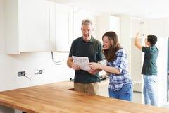 Vrouw met Timmerman Looking At Plans voor Nieuwe Keuken stock fotografie