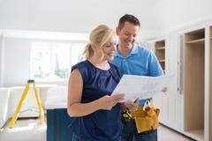 Vrouw met Timmerman Looking At Plans voor Nieuwe Keuken royalty-vrije stock fotografie