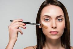 Vrouw met toon- stichting op gezicht stock fotografie