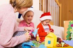 Vrouw met twee meisjes die voor Kerstmis voorbereidingen treffen Stock Foto's
