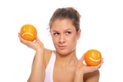 Vrouw met twee sinaasappelen verschillende emoties Royalty-vrije Stock Foto's