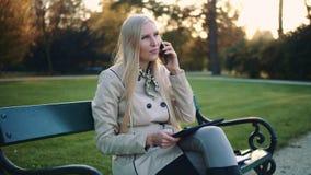 Vrouw met van tabletcomputer en cellphone zitting op parkbank stock videobeelden