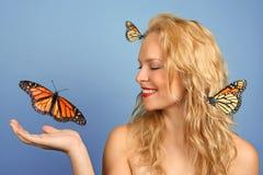 Vrouw met Vele in Hand Vlinders en Haar Haar Stock Afbeeldingen
