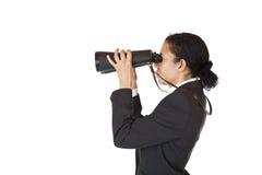 Vrouw met verrekijkers die naar zaken zoeken Stock Foto's