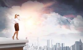 Vrouw met verrekijkers op wolkenkrabberdak Royalty-vrije Stock Afbeelding