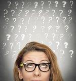 Vrouw met in verwarring gebrachte gezichtsuitdrukking en vraagtekens boven hoofd Stock Foto