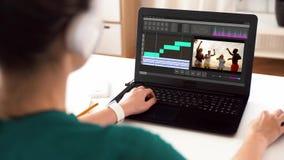 Vrouw met videoredacteursprogramma over laptop thuis stock footage