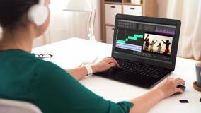 Vrouw met videoredacteursprogramma over laptop thuis stock video