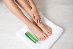 Vrouw met vlotte voeten, wit handdoek en schoonheidsmiddel op lichte achtergrond, hoogste mening royalty-vrije stock foto