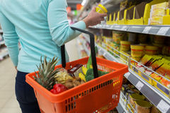 Vrouw met voedselmand en kruik bij kruidenierswinkelopslag Stock Foto's