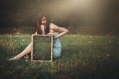Vrouw met vreemde spiegel op een weide royalty-vrije stock afbeelding