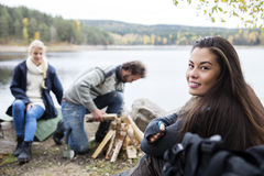 Vrouw met Vrienden die Vuur bij Oever van het meer het Kamperen voorbereiden royalty-vrije stock fotografie