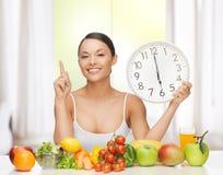 Vrouw met vruchten, groenten en klok stock afbeeldingen