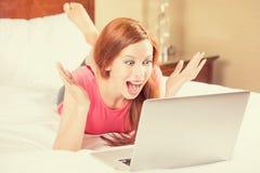 Vrouw met wapens het opgeheven gebruiken die het haar laptop scherm bekijken Stock Foto's